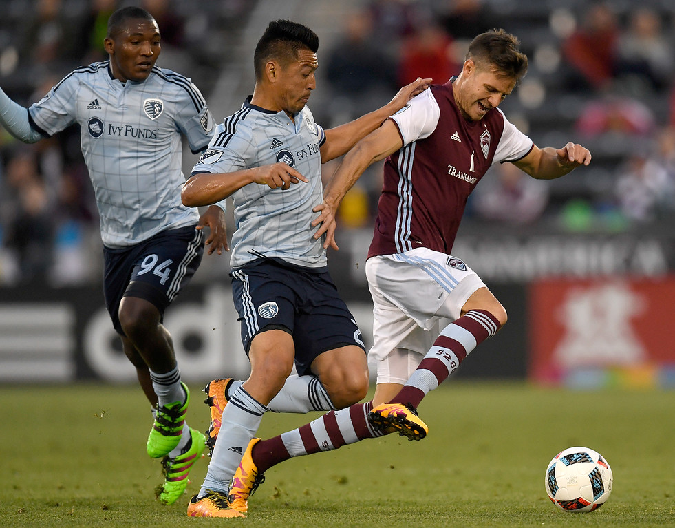 . COMMERCE CITY, CO - MAY 11: Luis Solignac (21) of Colorado Rapids is defended by Roger Espinoza (27) of Sporting Kansas City as Jimmy Medranda (94) looks on during the first half of action. The Colorado Rapids hosted Sporting Kansas City on Wednesday, May 11, 2016. (Photo by AAron Ontiveroz/The Denver Post)