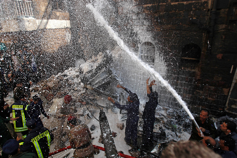 . Yemeni soldiers and firefighters work to extinguish fire at the site of a plane crash in Sanaa, Yemen, Tuesday, Feb. 19, 2013. A Yemeni official says a military plane on a training exercise crashed into a neighborhood in the country\'s capital, Sanaa, killing and injuring scores of people. (AP Photo/Hani Mohammed)