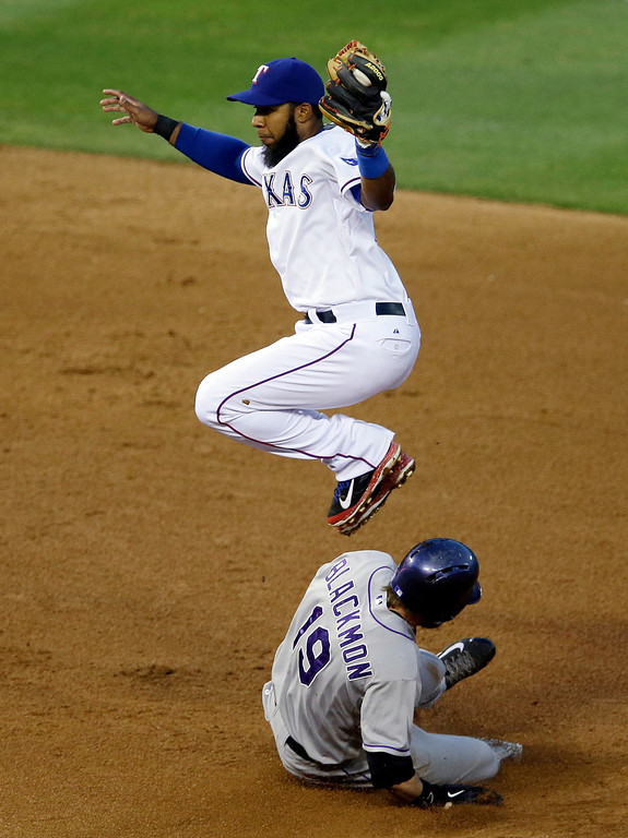 . Colorado Rockies\' Charlie Blackmon (19) steals second safely as Texas Rangers\' Elvis Andrus has to leap to grab a high throw from the plate in the fourth inning of a baseball game, Wednesday, May 7, 2014, in Arlington, Texas. (AP Photo/Tony Gutierrez)