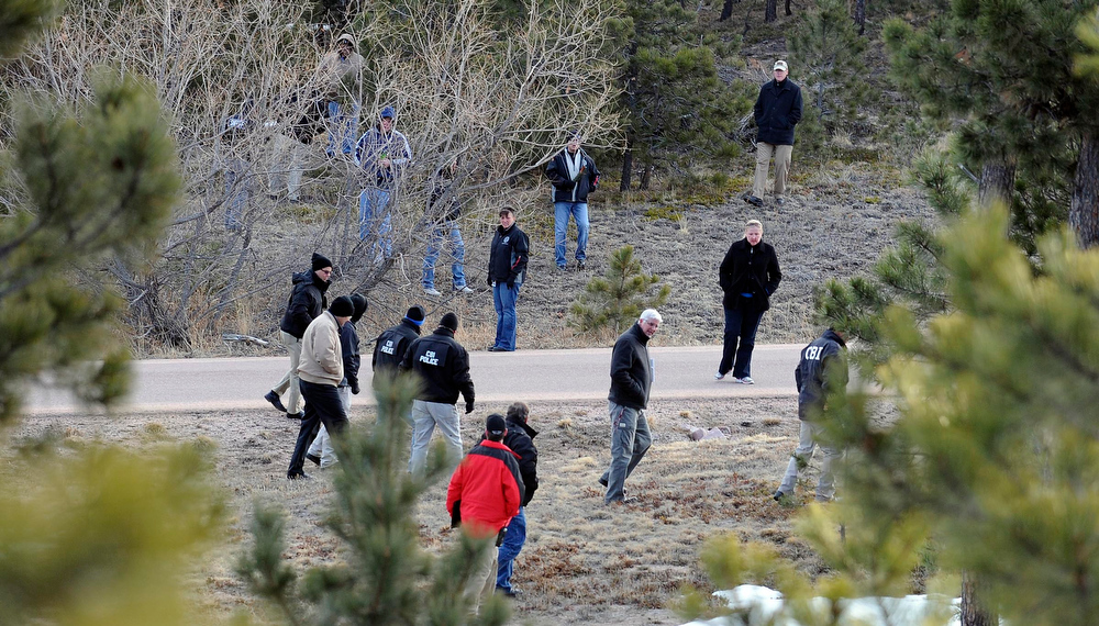 . Investigators search the wooded area surrounding the home of Tom Clements, executive director of the Colorado Dept. of Corrections on Colonial Park Dr. east of Monument Wednesday morning. (Photo By Steve Nehf / The Denver Post)