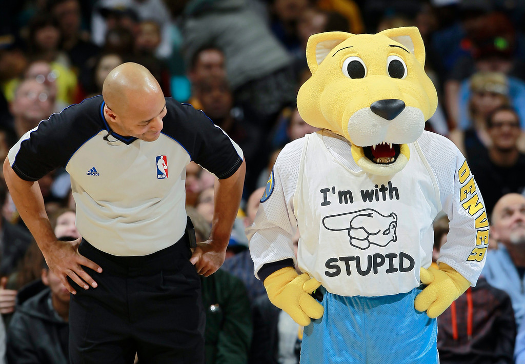 . Refere Marc Davis, left, gets a better look at a shirt worn by Denver Nuggets mascot Rocky the mountain lion during a timeout on the floor as the Nuggets host the Los Angeles Clippers in an NBA basketball game in Denver, Monday, Feb. 3, 2014. (AP Photo/David Zalubowski)
