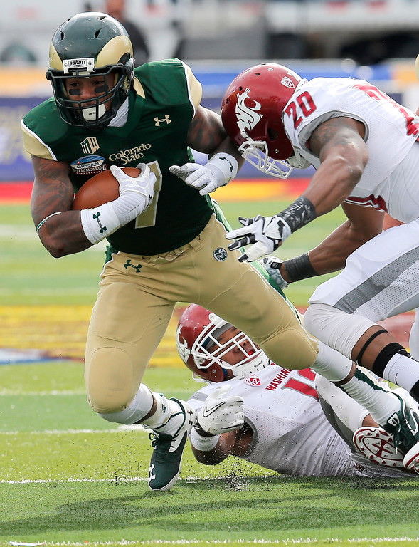. Colorado State running back Donnell Alexander (7) is hit by Washington State  cornerback Nolan Washington (20) during the first half of the New Mexico Bowl NCAA college football game, Saturday, Dec. 21, 2013, in Albuquerque, N.M. (AP Photo/Matt York)