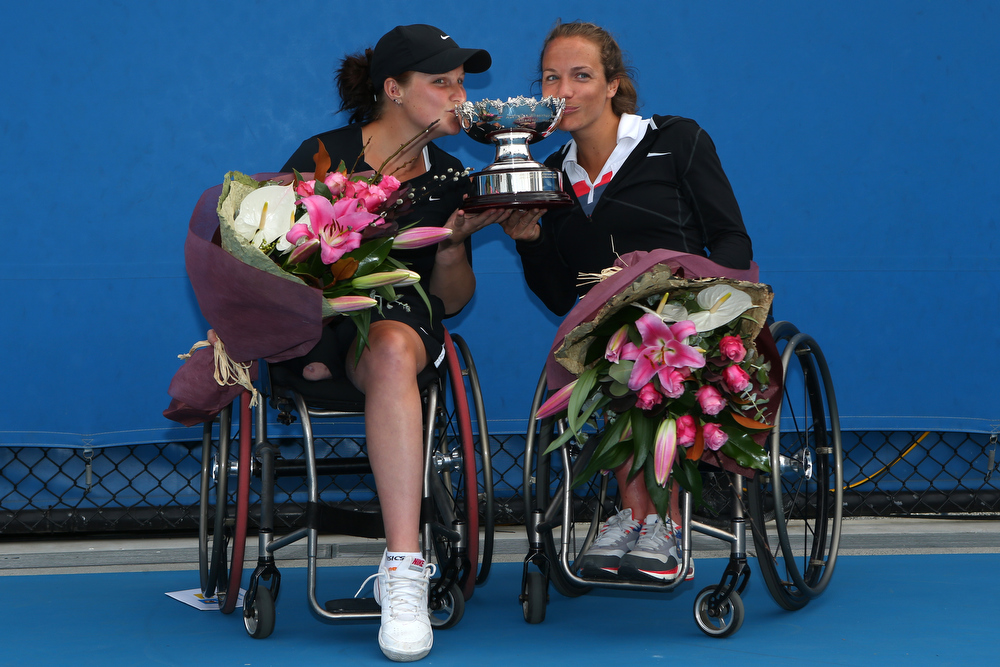 Description of . Jiske Griffioen of the Netherlands and Aniek Van Koot of the Netherlands pose with the trophy after winning their Women's Wheelchair Doubles Final match against Lucy Shuker of Great Britain and Marjolein Buis of the Netherlands during day twelve of the 2013 Australian Open at Melbourne Park on January 25, 2013 in Melbourne, Australia.  (Photo by Robert Prezioso/Getty Images)
