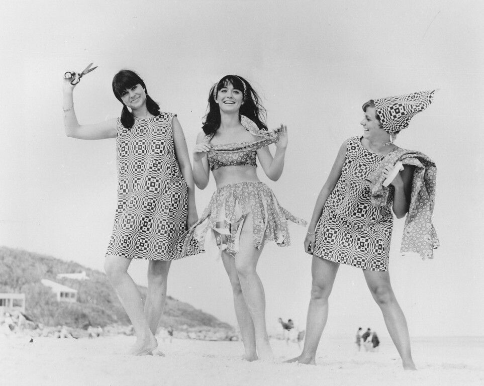 . 1966: The Inheritor, representing a generation of American men and women, ages 25 and younger. College students Susie Bohn, left, Anne McKee and an unidentified friend model mail order disposable paper dresses manufactured by Scott Paper Co., on their visit to Bermuda on April 27, 1966. The dresses are made of layers of paper with rayon scrim in between. Bohn, who is wearing the black and white Op Art design, transformed McKee\'s bandana-patterned paper dress into a halter top, hula skirt and headband. (AP Photo)