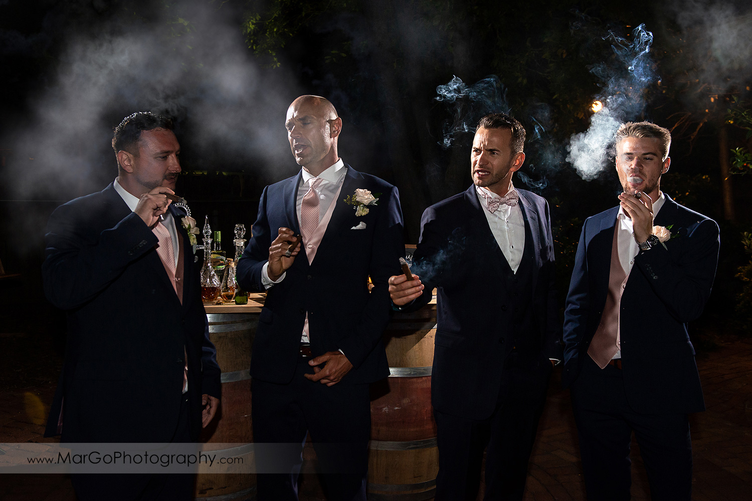 groom and groomsmen smoking cigars during wedding reception at San Pablo Rockefeller Lodge