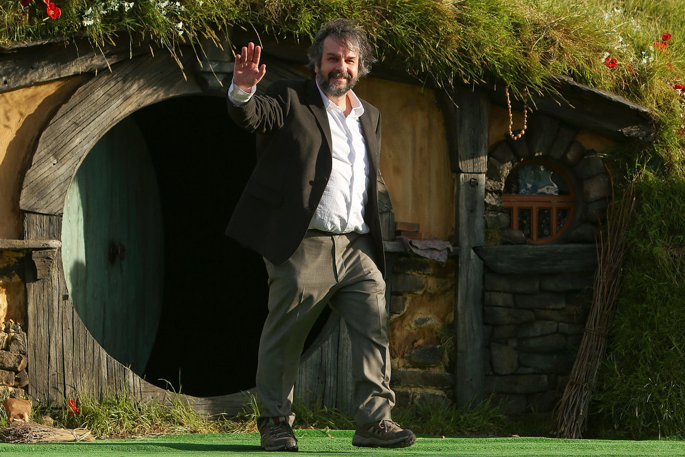 Description of . Director Sir Peter Jackson emerges from from a Hobbit house before delivering a speech at the