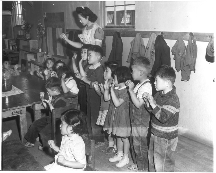"""""""Japanese Tots Sing English Songs -- A kindergarten tots under supervision of Aiko Sumoge, assistant teacher, sing an English folk song in class at the Tule Lake, California, Japanese relocation center.""""--caption on photograph"""