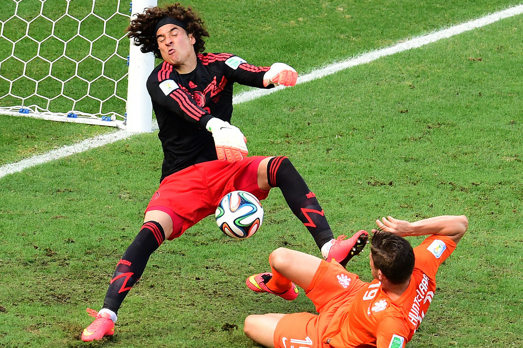. Netherlands\' forward Klaas-Jan Huntelaar (R) shoots towards Mexico\'s goalkeeper Guillermo Ochoa during a Round of 16 football match between Netherlands and Mexico at Castelao Stadium in Fortaleza during the 2014 FIFA World Cup on June 29, 2014. AFP PHOTO / JAVIER SORIANO