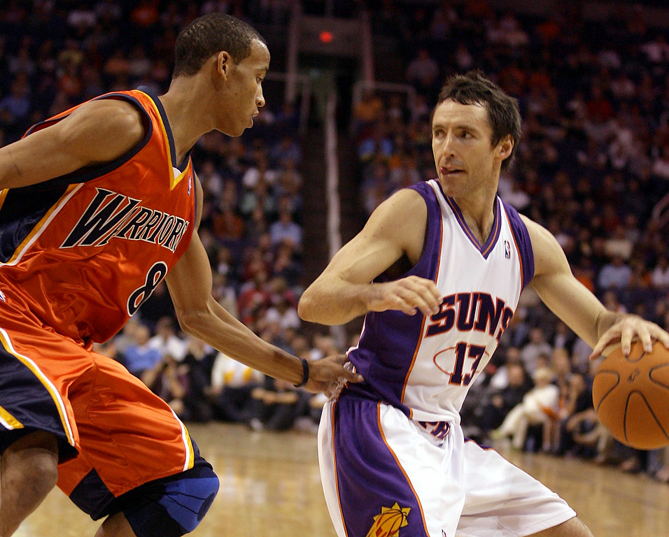 . Golden State Warriors guard Monta Ellis, left, hand-checks Phoenix Suns guard Steve Nash, right, as Nash looks for an open teammate to pass to in the first quarter of a basketball game Friday, Dec. 15, 2006, in Phoenix.(AP Photo/Paul Connors)