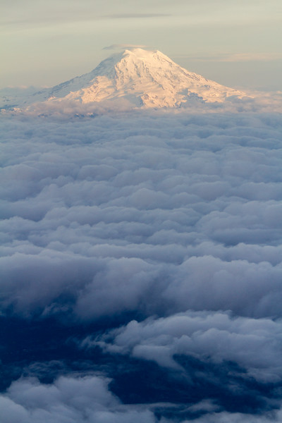 View of clouds below snowcapped mountain - USA - Hawaii