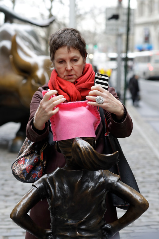 ". A woman places a pink hat on a statue of a fearless girl, Wednesday, March 8, 2017, in New York. The statue was installed by an investment firm in honor of International Women\'s Day. An inscription at the base reads, ""Know the power of women in leadership. She makes a difference. State Street Global Advisors.\"" (AP Photo/Mark Lennihan)"
