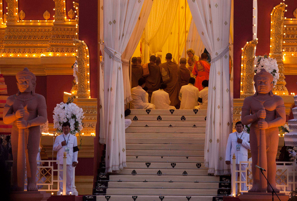 ". Cambodian King Norodom Sihamoni, facing camera on right in background, son of the late King Norodom Sihanouk, and his mother, Queen Norodom Monineath, behind him, pray inside the crematorium where the body of Sihanouk rests in Phnom Penh, Cambodia, Monday, Feb. 4, 2013. Hundreds of thousands of mourners gathered in Cambodia\'s capital Monday for the cremation of Sihanouk, the revered ""King-Father,\"" who survived wars and the murderous Khmer Rouge regime to hold center stage in the Southeast Asian nation for more than half a century. (AP Photo/David Guttenfelder)"