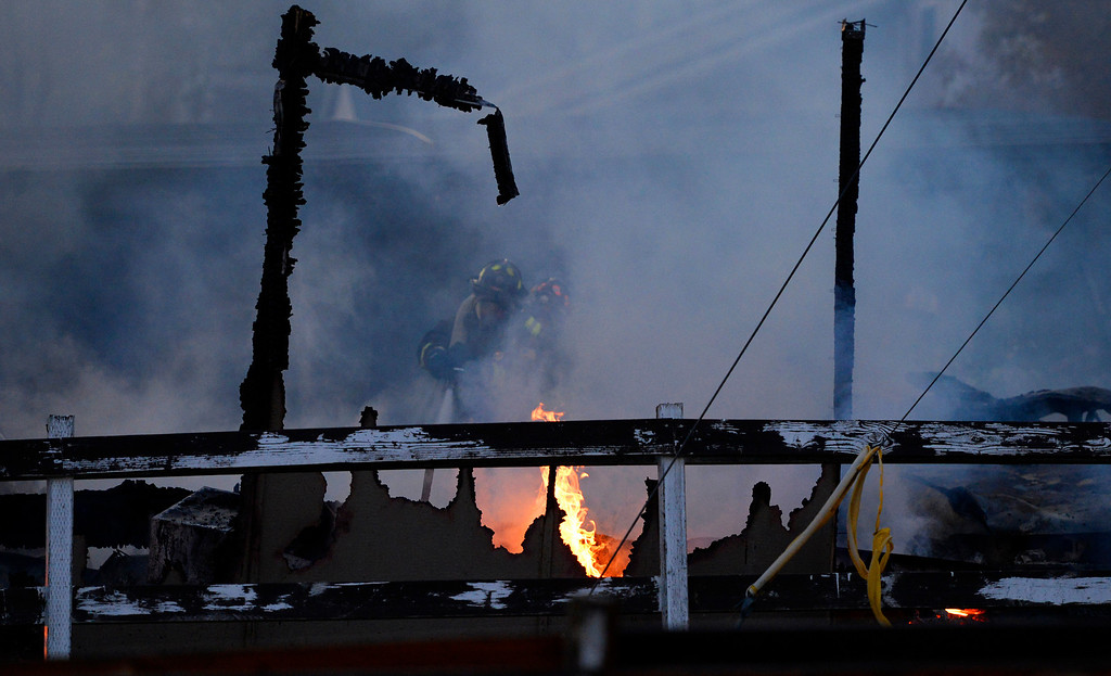 . Fire crews work on putting out a fire near Estes Street and Alameda Boulevard in Lakewood, October 22, 2013.  (Photo By RJ Sangosti/The Denver Post)