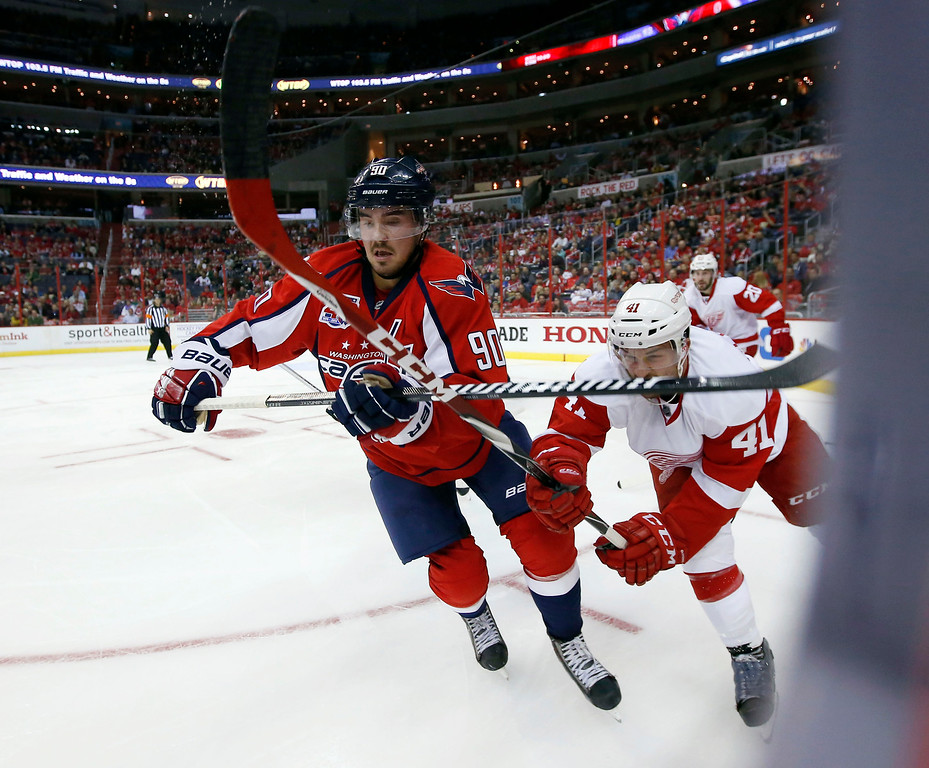 . Washington Capitals left wing Marcus Johansson (90), from Sweden, and Detroit Red Wings right wing Luke Glendening (41) skate after the puck in the second period of an NHL hockey game, Wednesday, Oct. 29, 2014, in Washington. (AP Photo/Alex Brandon)