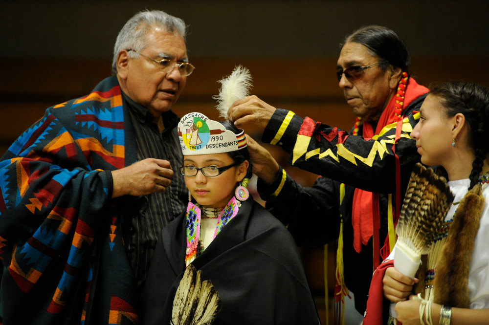 . Tom Ware, third from left, adjusts a feather in the head gear of newly crowned Sand Creek Massacre Descendants Trust Princess, Samantha Wells, 11-years-old, second from left, as Samantha\'s grandfather, Robert Simpson, left, and outgoing princess, Kelsey Palmer, 16, right, witness the ceremony at the 22nd annual Sand Creek Descendants Gathering in Anadarko Oklahoma, Saturday, December 1st, 2012. Nearly 100 descendants of the Sand Creek Massacre gathered at the Anadarko High School gym for traditional Gourd dancing, food and other activities and also to get updates on legal action towards the U.S. for the massacre which left over 150 Cheyenne and Arapaho Indians dead in southeast Colorado November 29th, 1864. The Denver Post/ Andy Cross