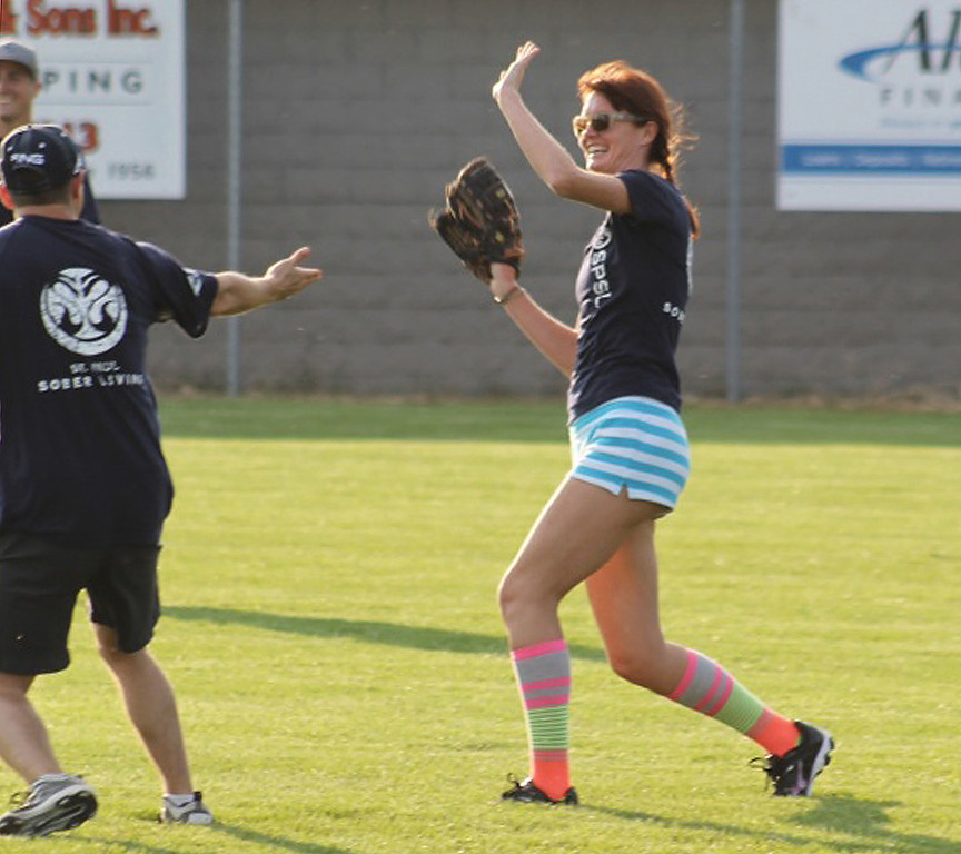. Katie S., left, today living in the Detroit area, gets a high-five from a teammate after making a catch during a Saints softball game sponsored by St. Paul Sober Living in summer 2013. The team\'s roster is comprised of adults living a sober lifestyle. (Courtesy photo)