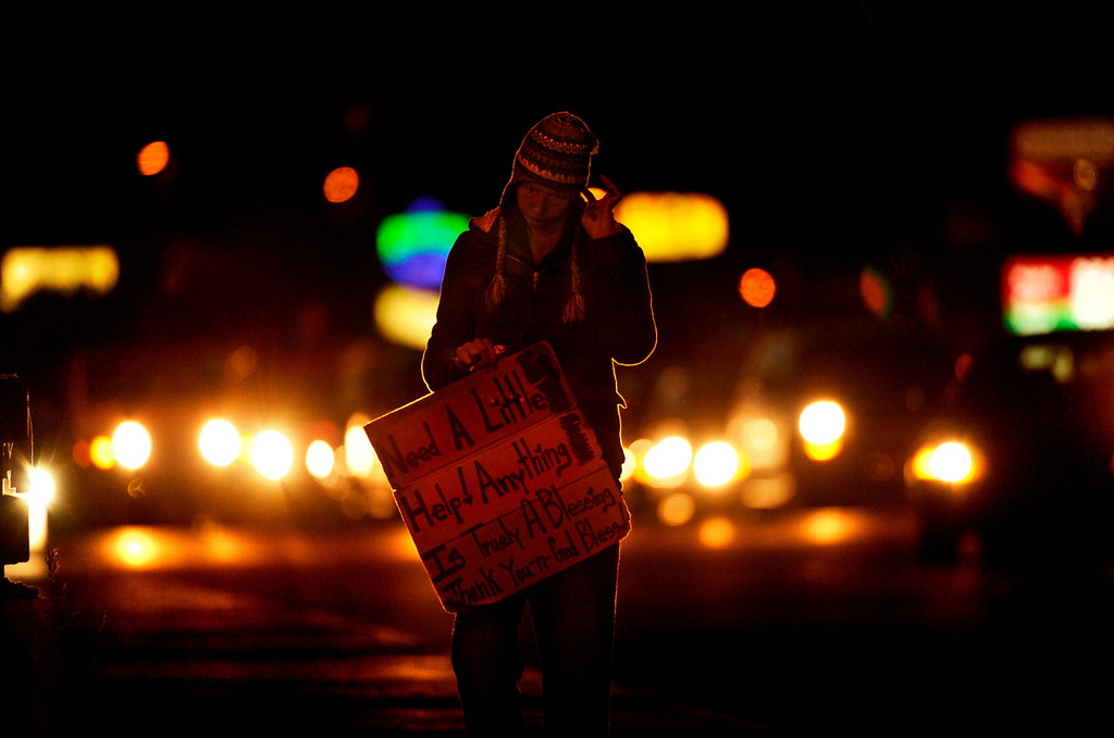 """. Angel flies her sign late into the night on a busy commuter road in Denver. She has not made enough money to buy a \""""wake-up\"""" shot of heroin. If she is can\'t shoot up immediately after sleeping, she will begin to feel withdrawal effects. Angel must shoot up four or five times a day. She spends around $30,000 a year trying to stay well."""