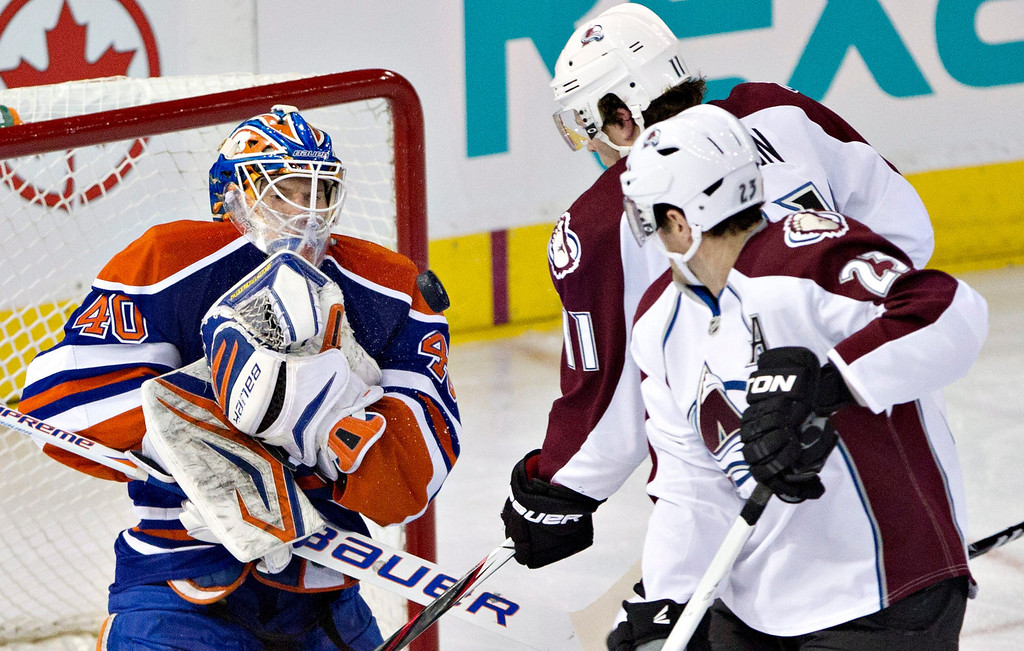 . Edmonton Oilers goalie Devan Dubnyk makes the save as Colorado Avalanche\'s Jamie McGinn and Milan Hejduk (23) look for the rebound during the second period of their NHL hockey game, Monday, Jan. 28, 2013, in Edmonton, Alberta. (AP Photo/The Canadian Press, Jason Franson)