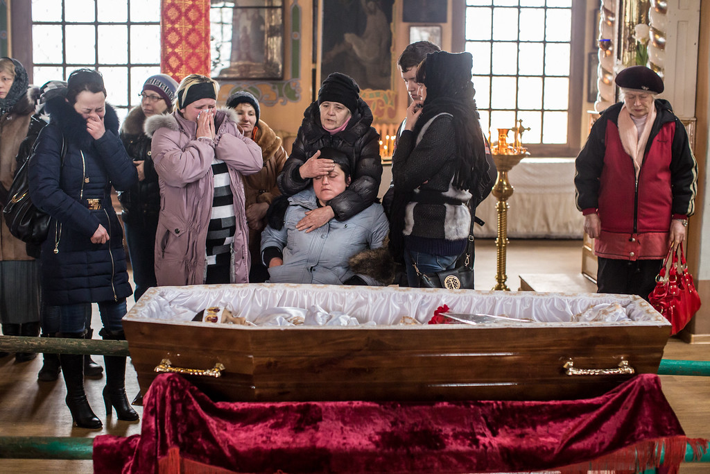 . ARTEMIVSK, UKRAINE - FEBRUARY 15: (EDITORS NOTE: Image contains graphic content.)  Zhanna Molodetskykh (C) attends the funeral of her son Igor Molodetskykh, 7, who was killed two days prior when a shell hit his school on February 15, 2015 in Artemivsk, Ukraine. A ceasefire scheduled to go into effect at midnight was reportedly observed along most of the front, save for near the embattled town of Debaltseve. (Photo by Brendan Hoffman/Getty Images)
