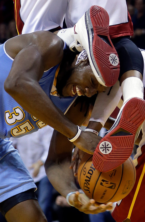 . Denver Nuggets forward Kenneth Faried (35) is fouled by Miami Heat guard Dwyane Wade, top, during the second half of an NBA basketball game in Miami, Friday, March 14, 2014. The Nuggets won 111-107. (AP Photo/Alan Diaz)