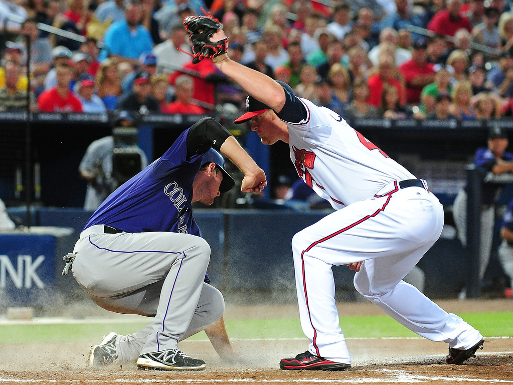 . D. J. LeMahieu #9 of the Colorado Rockies scores on a wild pitch against David Carpenter #48 of the Atlanta Braves at Turner Field on July 29, 2013 in Atlanta, Georgia. (Photo by Scott Cunningham/Getty Images)