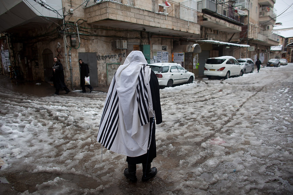 . An Ultra-orthodox Jewish man wears a praying shawl in the snow in the Mea Shearim religious neighborhood on January 10, 2013 in Jerusalem, Israel. (Photo by Uriel Sinai/Getty Images)