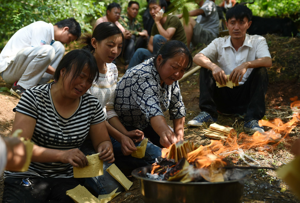 . Relatives of 71-year-old family matriarch He Guixiu burn paper money beside her body in a ceremony after she was found in a collapsed house at Longtoushan, in China\'s southwest Yunnan province on August 5, 2014.    AFP PHOTO/Greg BAKER/AFP/Getty Images