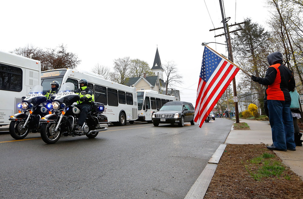 . Richard Corapi holds up an American flag as the limousine carrying family and friends drives through town following the funeral for the slain Massachusetts Institute of Technology (MIT) police officer Sean Collier near St Patrick\'s Church on April 23, 2013 in Stoneham, Massachusetts. Collier was allegedly shot by the suspects in the Boston Marathon bombing, Dzhokhar A. Tsarnaev, 19, and his brother Tamerlan Tsarnaev, 26, after their identities were determined and a manhunt was launched.  Tamerlan Tsarnaev was subsequently shot and killed after a car chase and shootout with police and Dzhokhar Tsarnaev was apprehended on a boat parked on a residential property in Watertown, Massachusetts. The bombing, on April 15 at the finish line of the marathon, killed three people and wounded at least 170.  (Photo by Jared Wickerham/Getty Images)