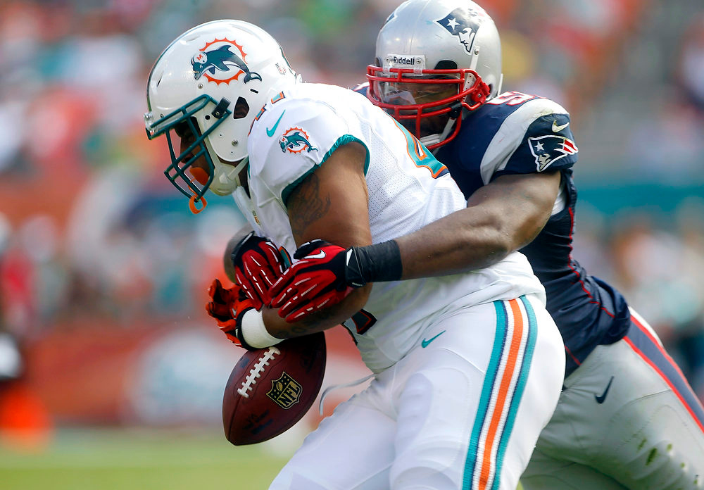 . Miami Dolphins fullback Jorvorskie Lane fumbles the ball as he is tackled by New England Patriots linebacker Jerod Mayo during the first half of an NFL football game, Sunday, Dec. 2, 2012, in Miami. The Dolphins recovered the ball. (AP Photo/John Bazemore)