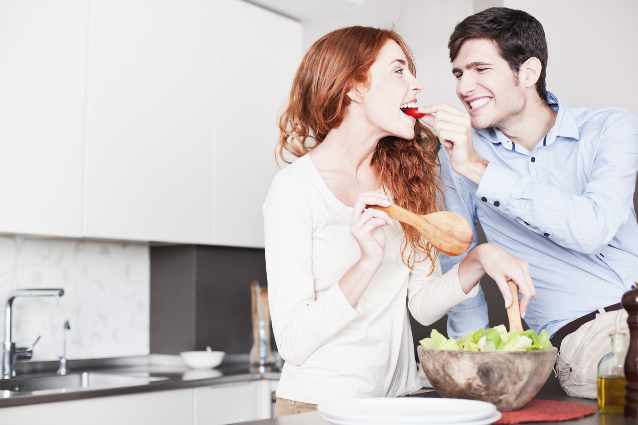 A young couple in their kitchen. She is redheaded and he has brown hair. More images of this lifwstyle series in port, including breakfast time, preparing salad and pasta. Made with professional make-up.