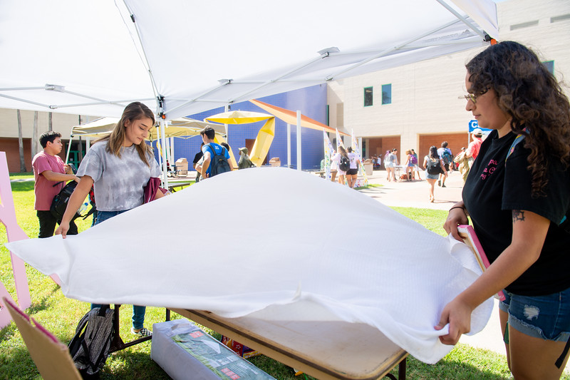 """Seana Uribe (left), and Emma Cardenas set up their table for the """"Get Your Greek on"""" event."""