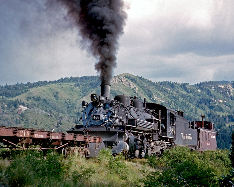 July 23, 1963. An afternoon Cumbres turn with 484 on the point and 488 pushing ahed of the caboose passes the old Coxo road crossing.