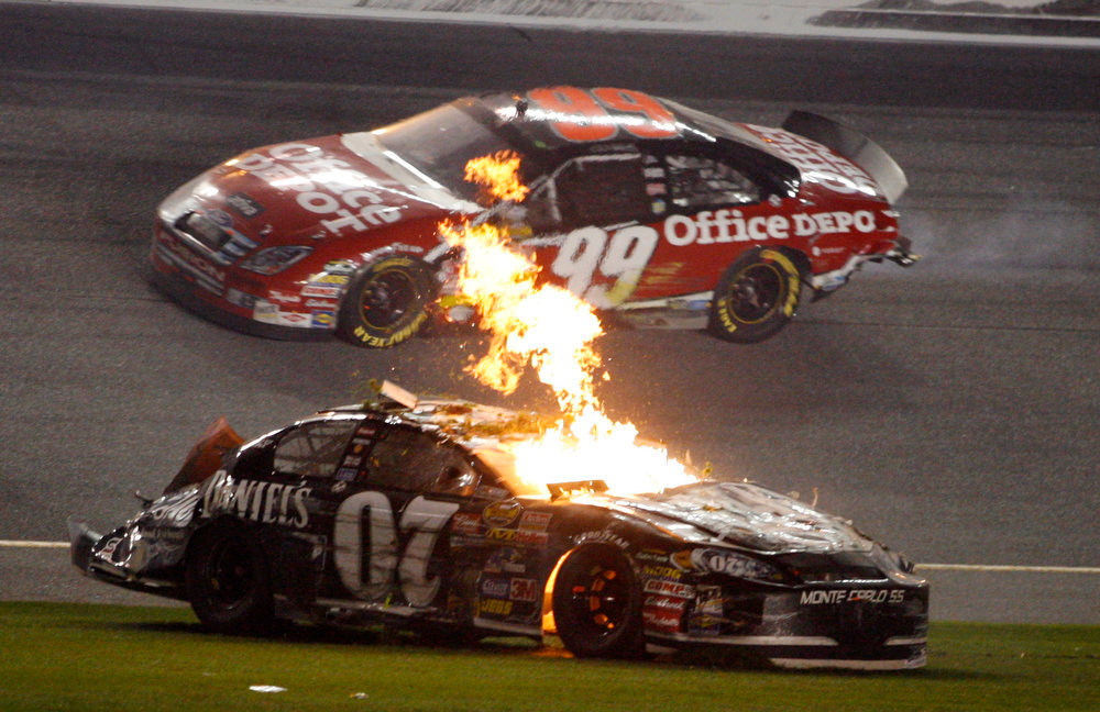Description of . Flames lick from Clint Bowyer's car, while Carl Edwards (99) passes by on the track following a crash on the last lap of the NASCAR Daytona 500 auto race at Daytona International Speedway in Daytona Beach, Fla., Sunday, Feb. 18, 2007. (AP Photo/Terry Renna)