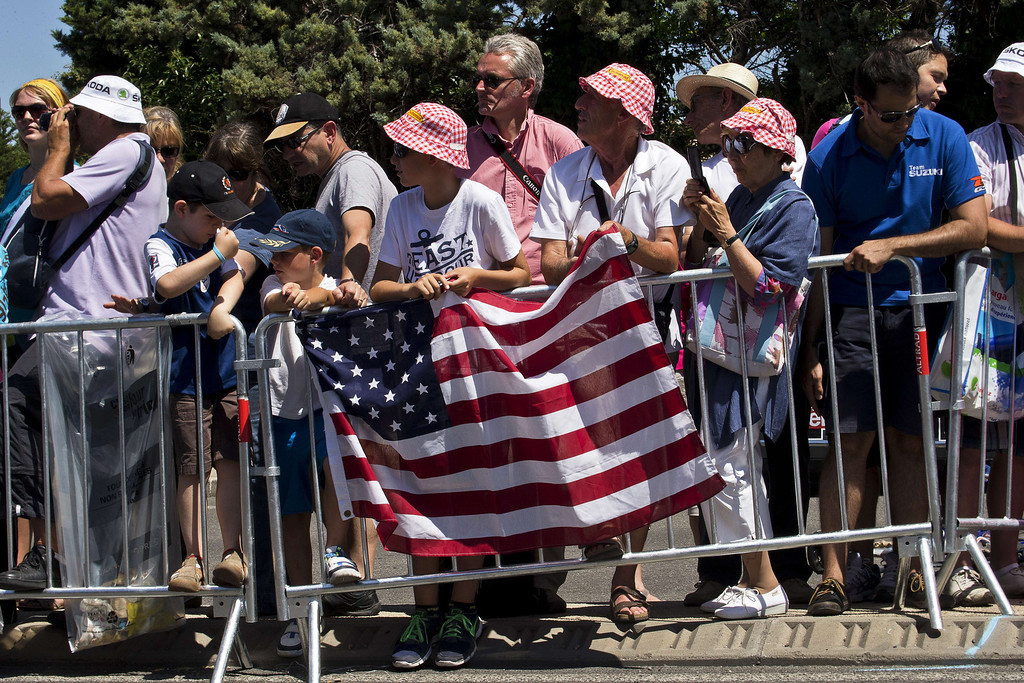. Supporters hold the national flag of the United States of America along the road on July 4, 2013, the USA\'s national day, as riders compete during the 176.5 km sixth stage of the 100th edition of the Tour de France cycling race between Aix-en-Provence and Montpellier, southern France. JOEL SAGET/AFP/Getty Images