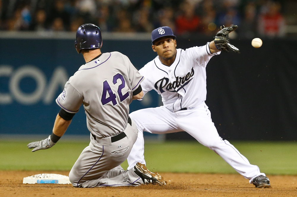 . San Diego Padres shortstop Alexi Amarista  takes in the throw from right fielder Chris Denorfia before putting the tag on Colorado Rockies\' DJ LeMahieu who is out trying to stretch a single in the sixth inning of a baseball game Tuesday, April 15, 2014, in San Diego. (AP Photo/Lenny Ignelzi)