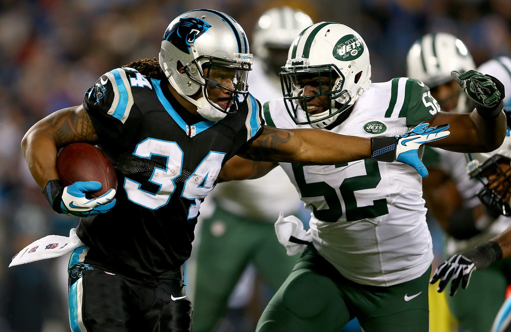 . David Harris #52 of the New York Jets tries to stop DeAngelo Williams #34 of the Carolina Panthers during their game at Bank of America Stadium on December 15, 2013 in Charlotte, North Carolina.  (Photo by Streeter Lecka/Getty Images)