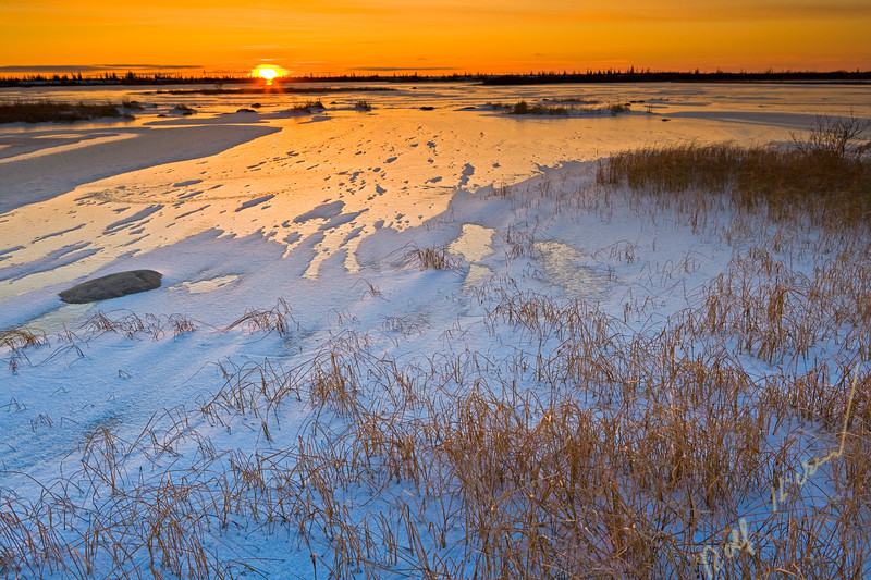 Sunset over a frozen lake in the Churchill Wildlife Management Area, Churchill, Manitoba, Hudson Bay, Canada.