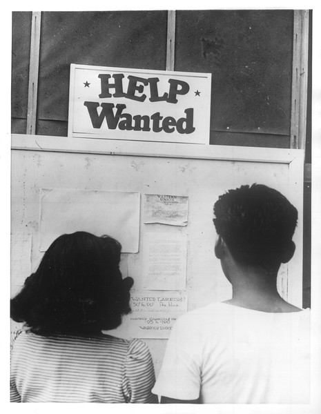"""""""Want A Job -- And Freedom -- Two young evacuees at Manzanar Relocation Center are pictured here studying 'Help Wanted' bulletins"""" -- caption on photograph"""