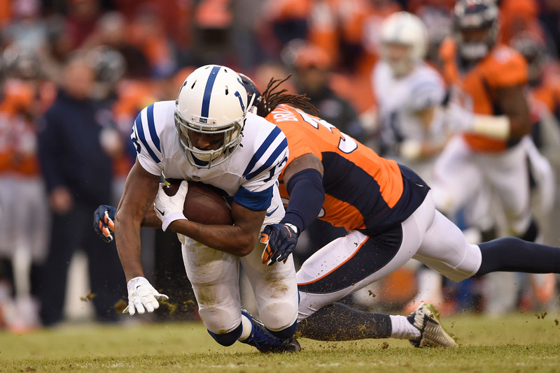 . T.Y. Hilton (13) of the Indianapolis Colts catches and is brought down by David Bruton (30) of the Denver Broncos in the first quarter. The Denver Broncos played the Indianapolis Colts in an AFC divisional playoff game at Sports Authority Field at Mile High in Denver on January 11, 2015. (Photo by AAron Ontiveroz/The Denver Post)