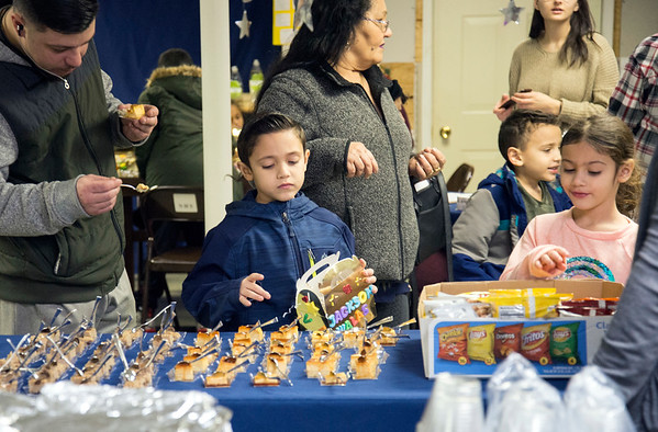01/06/19 Wesley Bunnell | StaffrrThree Kings Day was celebrated at Neighborhood Services of New Britain at 223 Broad St for families on Monday night. Richard Walas, L, looks over desserts with his son Jackson Richard Walas, age 7 , and daughter Cosima Walas, age 6.