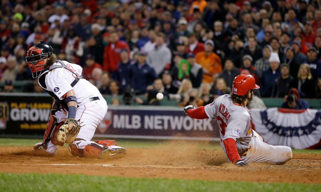 . St. Louis Cardinals\' Pete Kozma scores on a sacrifice fly as Boston Red Sox catcher Jarrod Saltalamacchia can\'t handle the throw during the seventh inning of Game 2 of baseball\'s World Series Thursday, Oct. 24, 2013, in Boston.  (AP Photo/Matt Slocum)