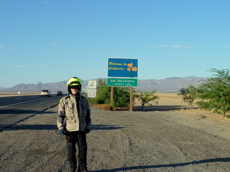 Peter, happy to be crossing into California. Note solar collector construction in the background.