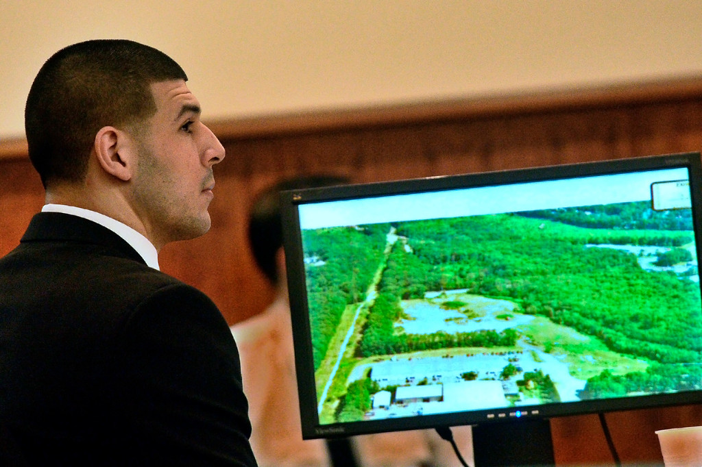. Former New England Patriots football player Aaron Hernandez listens during his murder trial as a prosecution exhibit is displayed, Friday, Jan. 30, 2015, in Fall River, Mass. Hernandez is charged with killing semiprofessional football player Odin Lloyd, 27, in June 2013. (AP Photo/The Boston Herald, Ted Fitzgerald, Pool)