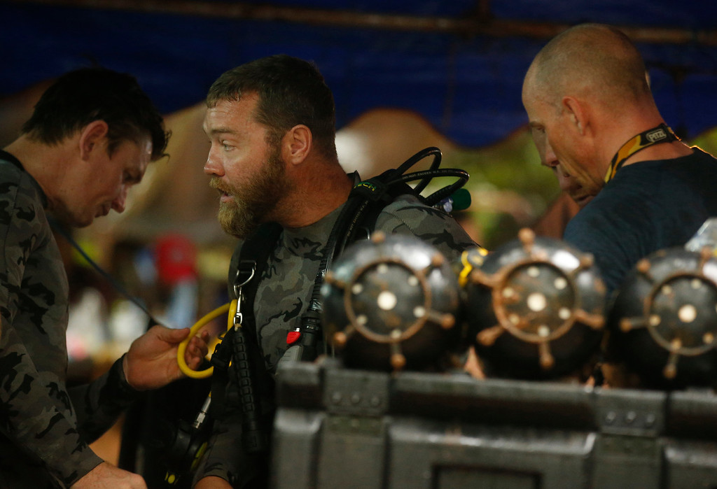 . Australian Federal Police and Defense Force personnel prepare for diving after the 12 boys and their soccer coach were found alive, in Mae Sai, Chiang Rai province, in northern Thailand, Tuesday, July 3, 2018. The 12 boys and soccer coach found after 10 days are mostly in stable medical condition and have received high-protein liquid food, officials said Tuesday, though it is not known when they will be able to go home. (AP Photo/Sakchai Lalit)