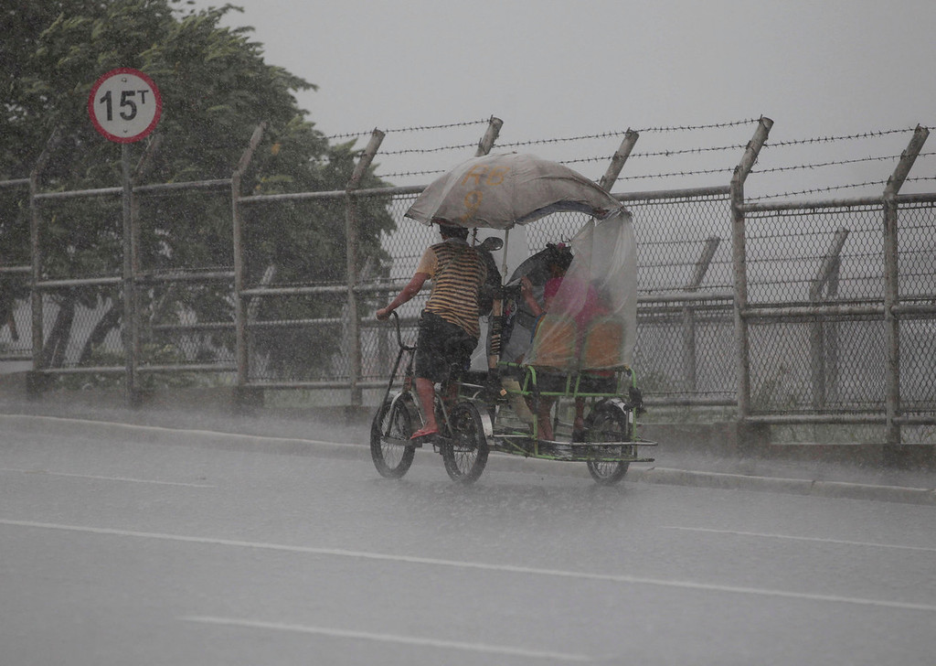 . A Filipino man pedals his pedicab during a brief rainfall at Navotas, north of Manila, Philippines on Monday, Aug. 12, 2013. Powerful Typhoon Utor battered the northern Philippines on Monday, toppling power lines and dumping heavy rains across mountains, cities and food-growing plain. The storm killed at least one man in a landslide and left 45 fishermen missing. (AP Photo/Aaron Favila)