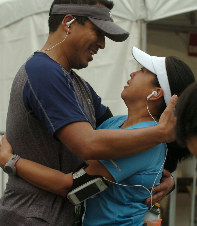 . Ronald Perez, 41, comforts his wife Divina Perez, 44, as she is overwhelmed after completion of her first L.A. Marathon in Santa Monica March 17, 2013. (Thomas R. Cordova/Staff Photographer)