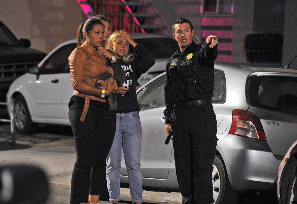 . In this image provided by the Santa Barbara Independent, people speak to a police officer after a mass shooting near the campus of the University of Santa Barbara in Isla Vista, Calif., Friday, May 23, 2014. A drive-by shooter went on a rampage near the Santa Barbara university campus that left seven people dead, including the attacker, and others wounded, authorities said Saturday. (AP Photo/Santa Barbara Independent, Paul Wellman)