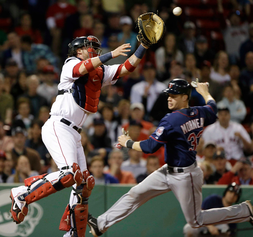 . Boston Red Sox catcher Jarrod Saltalamacchia reaches for a high throw as Minnesota Twins\' Justin Morneau slides in to score on a grounder by Ryan Doumit during the eighth inning of a baseball game at Fenway Park in Boston, Tuesday, May 7, 2013. (AP Photo/Elise Amendola)