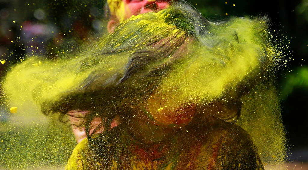 . An Indian woman shakes her head covered in colored powder as she celebrates Holi, the Hindu festival of colors, in Mumbai India, Monday, March 17, 2014. The festival heralds the arrival of spring. (AP Photo/ Rafiq Maqbool)