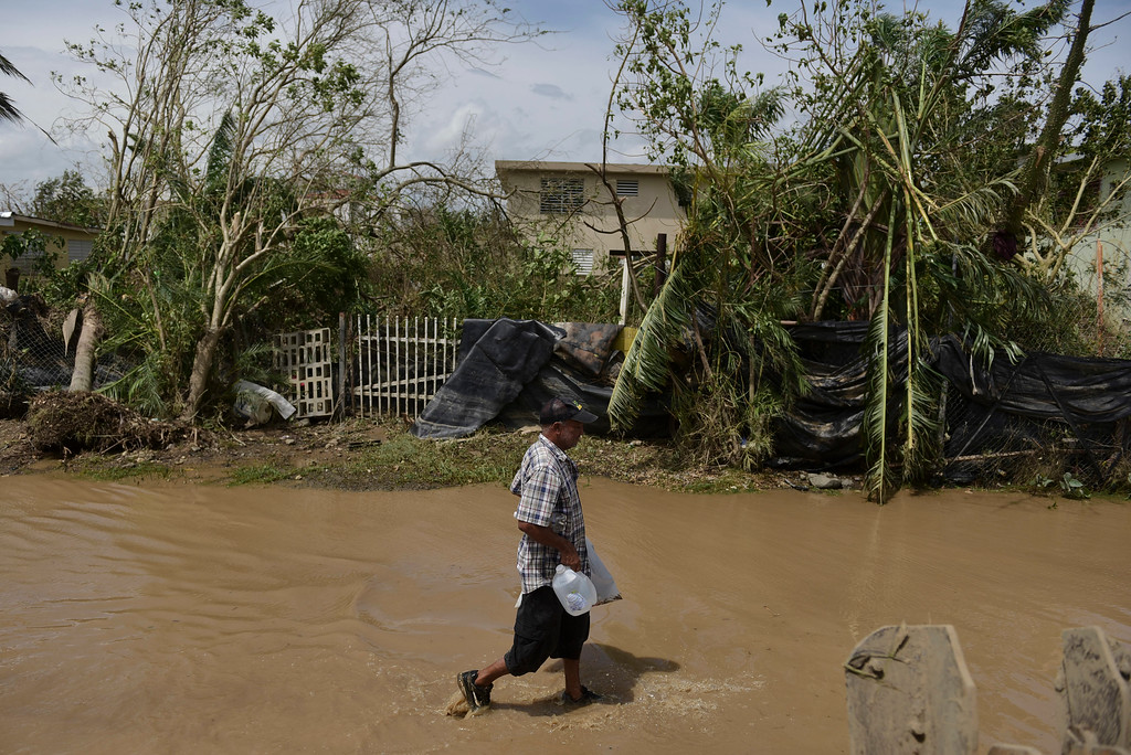 . A resident walks on a flooded road after the passing of Hurricane Maria, in Toa Baja, Puerto Rico, Friday, September 22, 2017. Because of the heavy rains brought by Maria, thousands of people were evacuated from Toa Baja after the municipal government opened the gates of the Rio La Plata Dam. (AP Photo/Carlos Giusti)